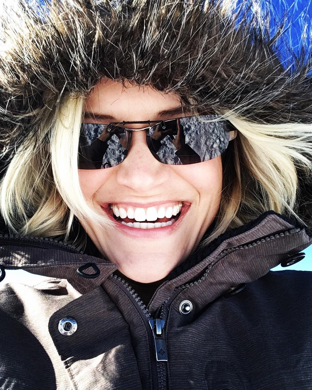 young woman smiling at you all bundled up wearing a warm winter coat